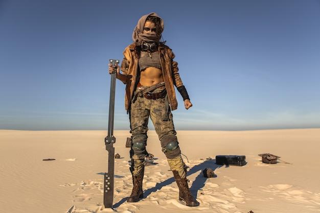 屋外で武器を持った終末後の女性。ぼろぼろの服を着た若いスリムな女の子の戦士