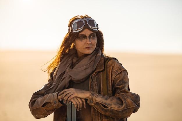 Постапокалиптическая женщина с оружием на открытом воздухе. молодая стройная девушка-воин в потрепанной одежде держит