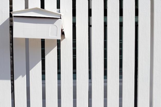 Почтовый ящик в белом деревянном заборе