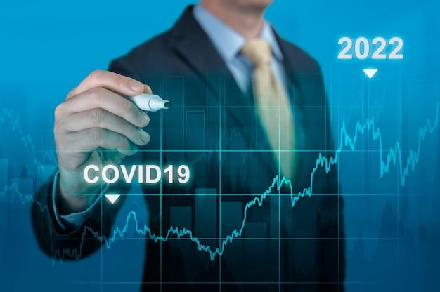2022年のコンセプトでのcovid-19後の景気回復。青い背景の上のマーカーポインティンググラフ成長計画とビジネスマンの手。 covid19パンデミックによる危機後の世界経済のタイムラインチャート図