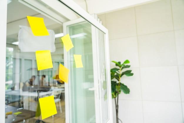 Папар для заметок на стеклянной доске в офисе проекта