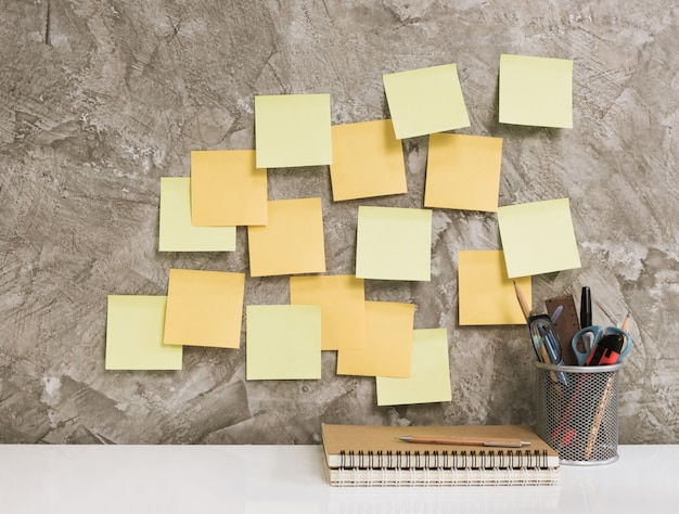 Post it,notebook,pencil,eyeglasses,pen,scissors and cactus on white table concrete background,work space concept