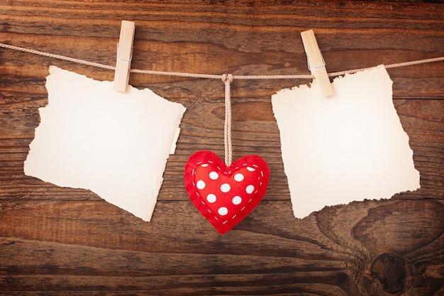 Разместите бумажную записку и сердечки на деревянном столе.