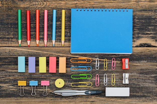 Post pandemic schooling concept with notebook, assorted school supplies on wooden table flat lay.