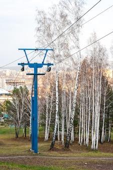 Столб с канатными дорогами рядом с березками осенью