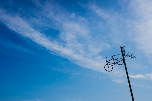 Post with the figure of some bicycles indicating the road, with blue sky and clouds in the background.
