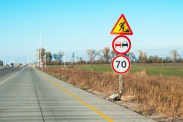 Post with warning road signs: road construction works, no passing and speed limit of 70 km/h