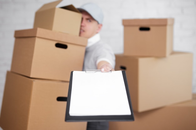 우편 배달 또는 이사하는 날 개념 - 서명할 클립보드를 제공하는 많은 상자를 가진 피곤한 남자