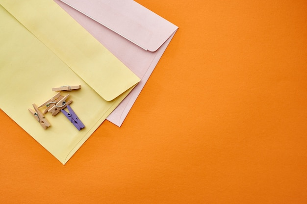 Почтовые конверты и скрепки крупным планом, оранжевая стена. канцелярские товары, школьные или образовательные принадлежности, инструменты для письма и рисования