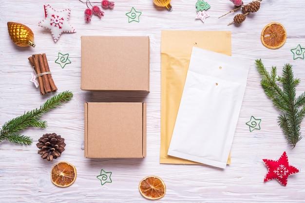 郵便包装、バブル封筒、木製のテーブル、クリスマスコンセプトの段ボール箱