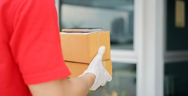 ボックスを運ぶと家の前に顧客に送信するのを待っている郵便労働者の男