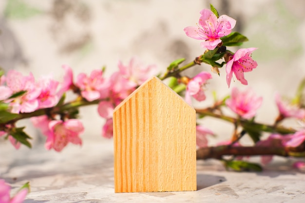 Postcard concept with a miniature wooden house. trending pink shades.