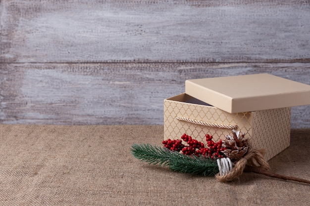 A postcard from a beige gift box with an open lid and a sprig of a christmas tree