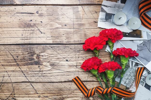 Открытка 9 мая - красная гвоздика лента георгия старые фотографии на деревянном фоне.