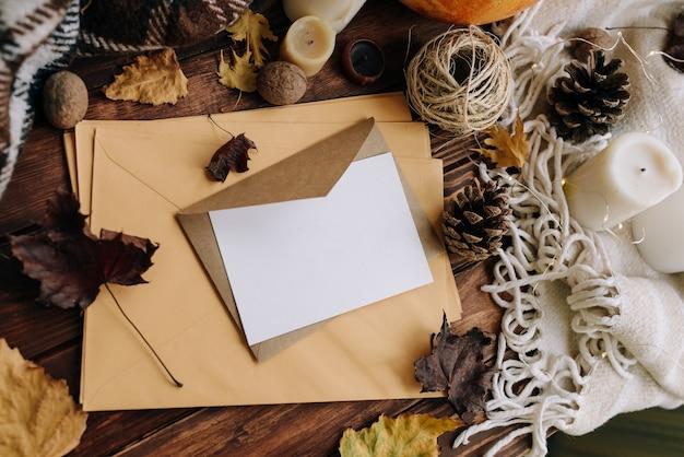 Открытка на желтом конверте на деревянном столе. осенняя композиция