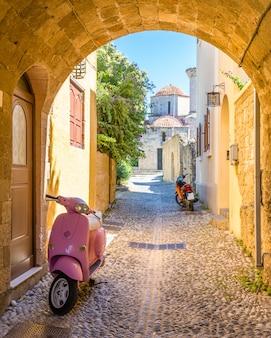 Открытка вид узкой улице с мотоциклом. родос, греция