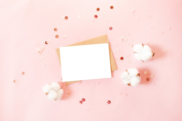 Postcard with craft paper envelope, glitter decor and cotton flowers on pink background