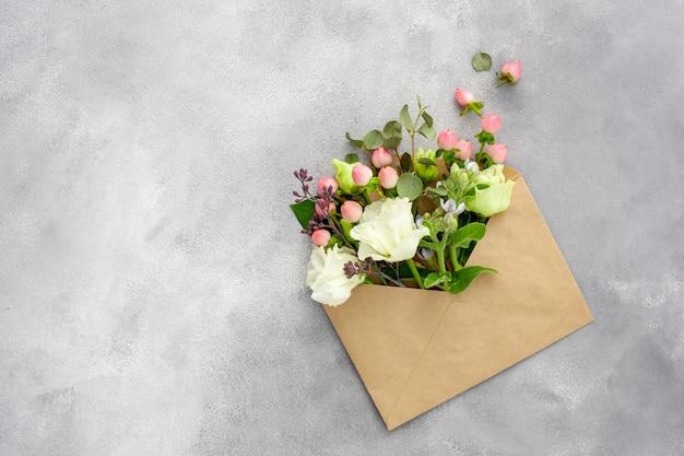 Открытка с раскрытым конвертом из крафт-бумаги, наполненным весенними цветами