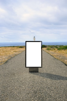 Poster billboard on the road to a lighthouse .blank advertising billboard mockup in the street