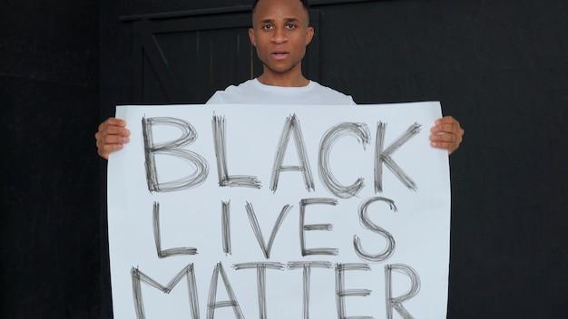 Плакат black lives matter в руках темнокожего мужчины