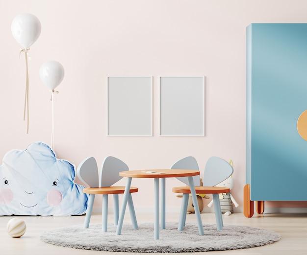 분홍색 벽, 다채로운 어린이 테이블 및 장난감이있는 어린이 방 내부의 포스터 프레임
