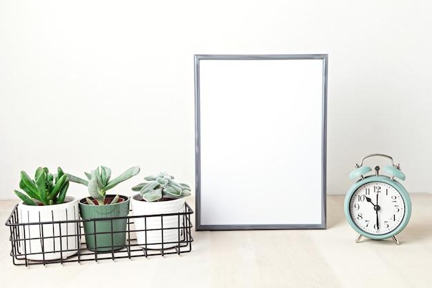 ポスターフレームのモックアップ、正面図、装飾要素、観葉植物、花、白い壁の上の空白のコピースペース。テキストまたは画像用のスペース