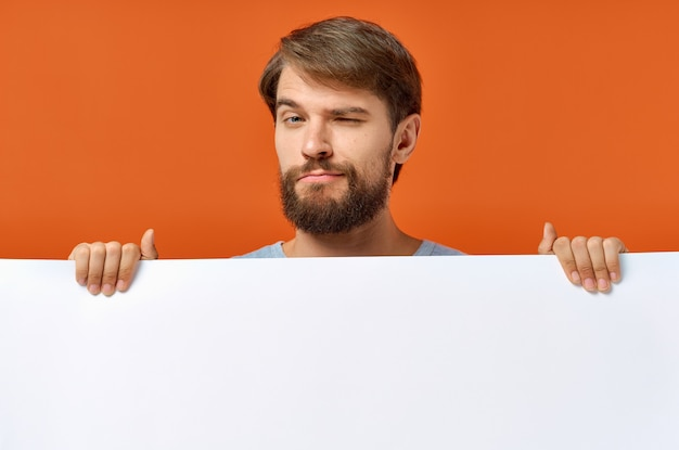 Poster mockup emotional guy holding a white sheet of paper. high quality photo