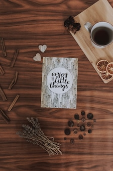 一杯のコーヒー、小さなポスター、乾いた草、小さなアクセサリーの横に貼られたポスター