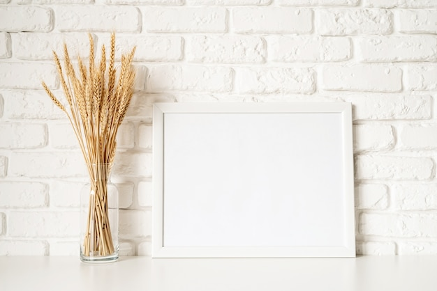 Poster template mock up with wheat decoration on white brick wall background. copy space