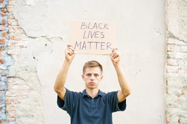 Плакат, в котором говорится, что черная жизнь имеет значение в руках молодого человека, кавказского парня устроил демон протеста ...