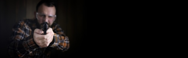 Плакат с пустым пространством для текста на фоне с бородатым мужчиной в защитных очках и тренировкой ушей в стрельбе из пистолета
