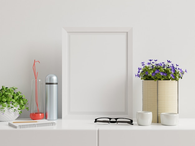 Poster with vertical frame on table and white wall