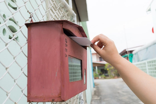 Posting a letter to red british postbox on street,