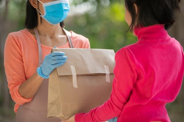 Il postino, il fattorino che indossa la maschera porta una piccola scatola consegnata al cliente davanti alla porta di casa. la donna che indossa la maschera previene il covid 19, l'epidemia di infezione da coronavirus. concetto di acquisto di consegna a domicilio.