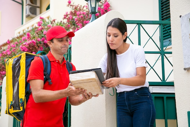 Postman holding clipboard with order data and woman signing it. caucasian courier with backpack wearing red uniform and delivering package or parcel to customer. delivery service and post concept
