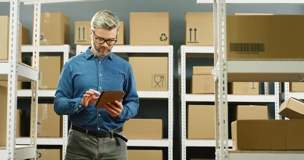 小包と郵便局に立って、タブレットコンピューターをタップするメガネの郵便配達。ボックスでいっぱいの分娩室で登録を行うコンピューターを持つ男性労働者。