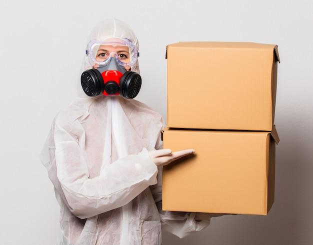 保護スーツとマスク付きメガネの郵便配達員は配達ボックスを保持します