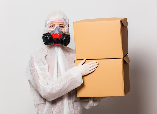 Postman in protection suit and glasses with mask holds delivery boxes