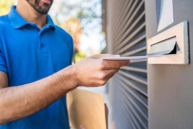 Почтальон положить письмо в почтовый ящик.