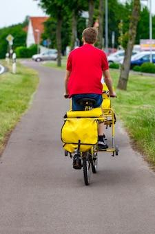 近所で郵便を運ぶ彼の貨物自転車に乗る郵便配達員。