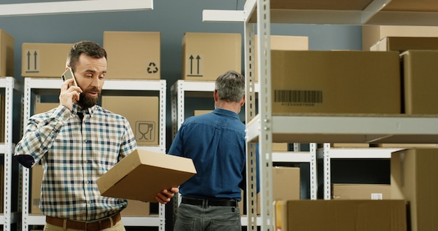 小包と郵便局に立って、携帯電話で話している郵便配達。男性労働者が携帯電話で話し、小包でいっぱいの配達室で小包を保持しています。
