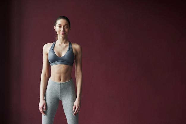 귀여운 여자의 postrait. 좋은 피트니스 체형을 가진 소녀는 공간이 넓은 방에서 운동을합니다.