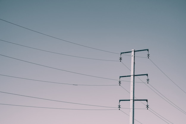 日光の下で空の背景に高電圧のワイヤーで投稿します。コピースペースのある空の多くのワイヤーのモノクロ背景画像。