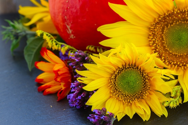 Posy of fresh mixed autumn flowers with raw pumpkin
