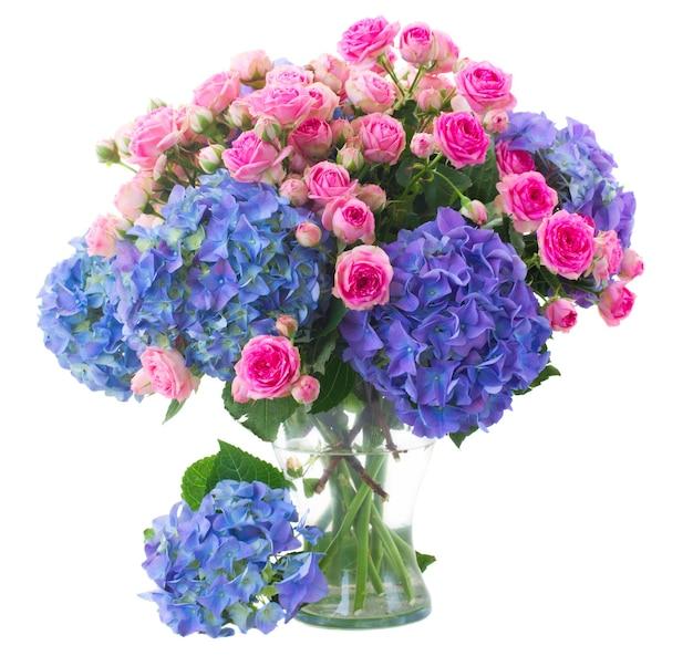 新鮮なピンクのバラと青いオルテンジアの花の花束は、白いスペースで隔離のガラスの花瓶にクローズアップ