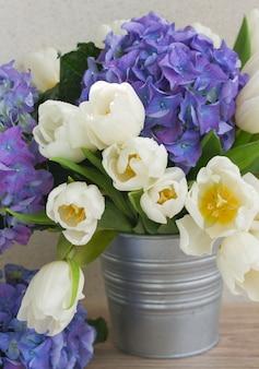 白いチューリップと青いアジサイの花の花束がクローズアップ
