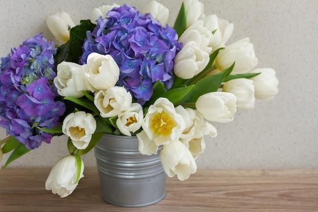 Букет из белых тюльпанов и цветов синей гортензии на столе