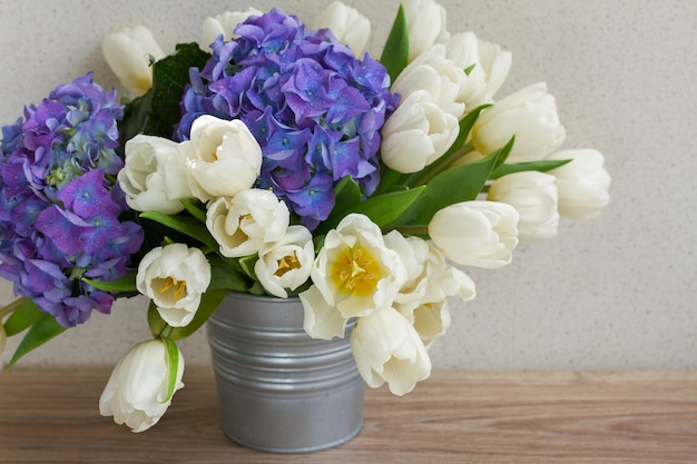Posy  of white tulips and blue hortensia flowers on table
