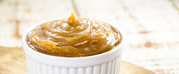 Pot of dulce de leche or homemade caramel on rustic wooden background, typical brazilian sweet