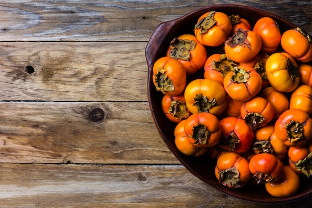Pot of fresh fruits persimmon kaki on wooden background
